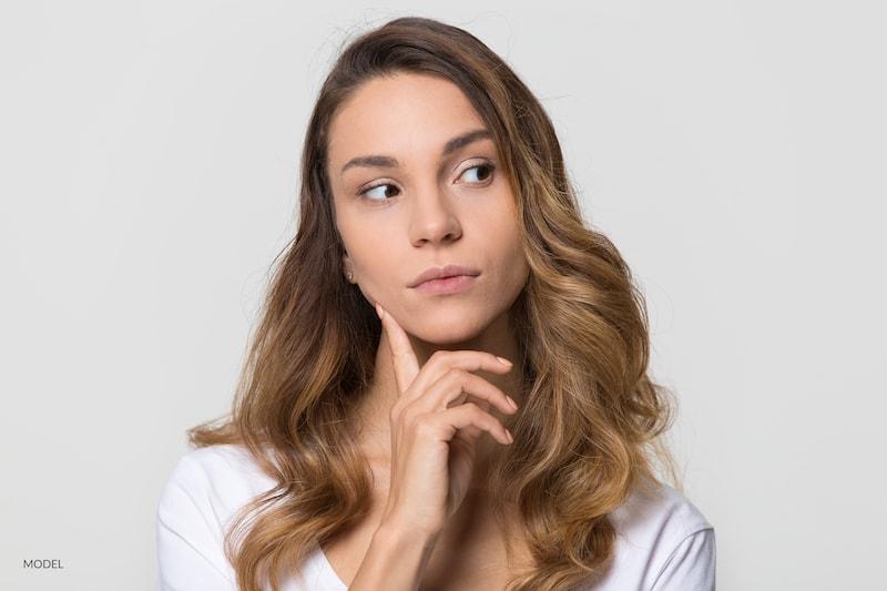 Thoughtful young woman looking away feeling doubt isolated on white studio wall