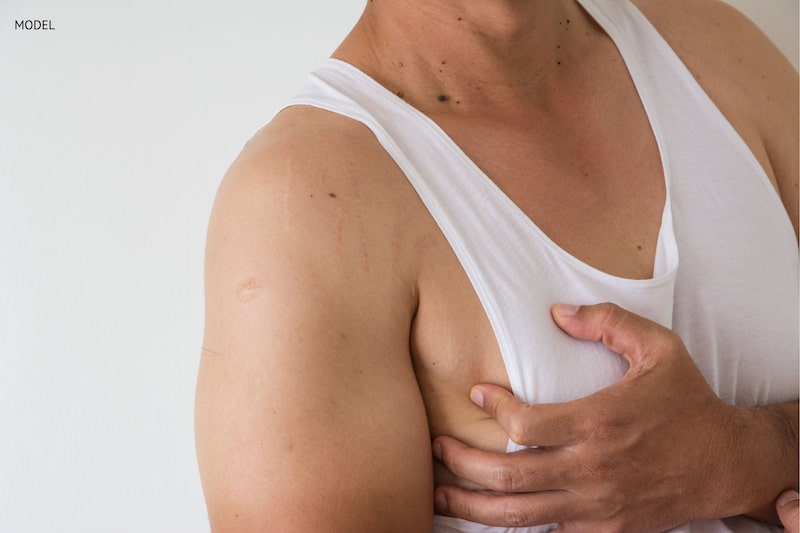 Man cupping his hand over his breast wearing a white t-shirt.
