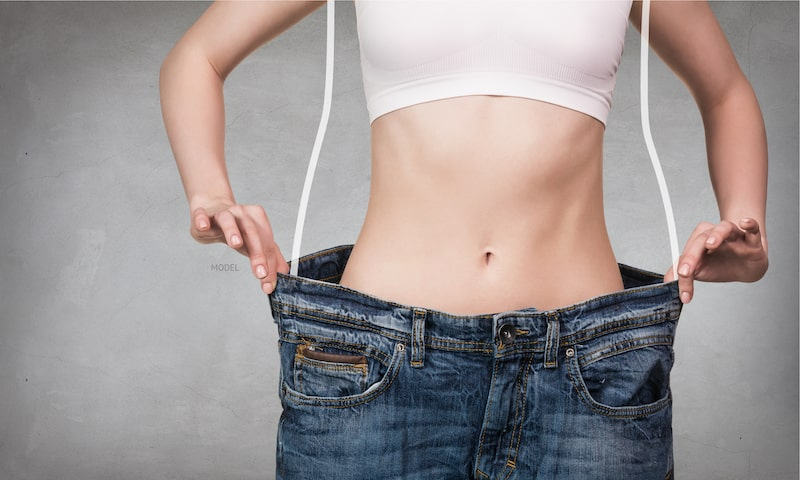 Woman wearing oversized jeans to demonstrate the concept of weight loss.